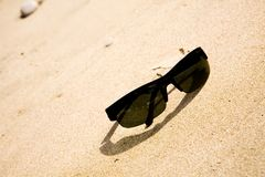 Black sunglasses on the sand. At sunny day Stock Photos