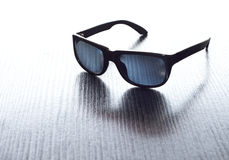 Black sunglasses on striated textured surface Stock Images