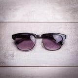 Black sunglasses on wood floor Stock Photos