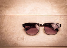 Black sunglasses on wood floor Royalty Free Stock Photos