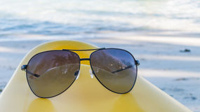 Black sunglasses on a yellow kayak and white beach background Royalty Free Stock Photos