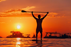 Black sunset silhouette of paddle boarder standing on SUP Royalty Free Stock Photos