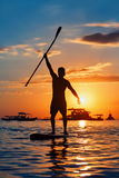 Black sunset silhouette of paddle boarder standing on SUP. Paddle boarder. Black sunset silhouette of young sportsman paddling on stand up paddleboard. Healthy Royalty Free Stock Photography