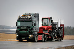 Black Super Scania Transports Forestry Machinery along Road Stock Photo