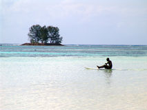 Black surfer floating in the ocean, and rowing oar. Seychelles Royalty Free Stock Photos