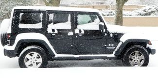 A black SUV car is contrasted sharply through fresh falling snow. A parked car is subjected to a ongoing snowfall that highlights its design elements by royalty free stock photos