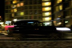Black suv car at night  with illuminated light city scene buildings and higway long exposure. Car speeding close up at the night with blurred motion long Royalty Free Stock Image