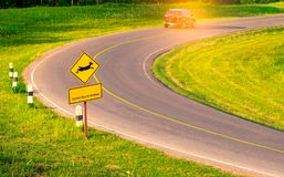 Black SUV car of the tourist driving with caution during travel. At curve asphalt road near yellow traffic sign with deer jumping inside the sign and have Royalty Free Stock Images