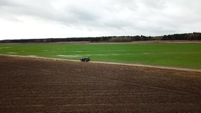 A black SUV driving on a field road. Aerial photography with quadcopter stock video