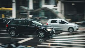 Black Suv Beside Grey Auv Crossing the Pedestrian Line during Daytime Royalty Free Stock Image