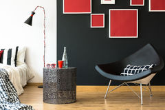 Swan chair in retro bedroom. Black swan chair in retro bedroom with red sunglasses and glass bottle on metal coffee table Royalty Free Stock Image