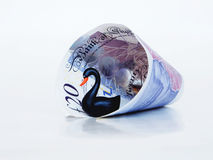 Black Swan Financial Risk. A black swan emerging from a rolled up £20 note Royalty Free Stock Photo