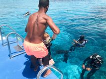 A black, swarthy, Arab athletic athletic man helping divers in black scuba diving suits with oxygen bottles sinks under the transp stock images