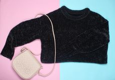 Black sweater, leather bag. On a pink background, minimalism, top view stock image