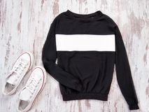 Black sweatshirt with a white stripe, white sneakers. Fashionable concept Stock Images
