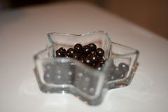 Black and sweet chocolate drop on crystal bowl Stock Photo