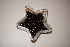 Black and sweet chocolate drop on crystal bowl Stock Photos