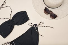Black swimsuit, hat and sunglasses. Beach wardrobe. Fashionable stock images