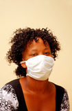 Ebola. Portrait of a beautiful young African American woman with black curly hair wearing a swine flu mask Stock Photos