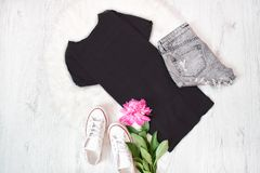 Black t-shirt, gray shorts, white sneakers and pink peony. Fashi Stock Photo