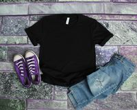 Black T Shirt mockup flat lay on purple brick background with pu. Rple shoes and ripped jeans royalty free stock photos