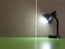 The black table lamp. On the green desk in front of cement wall background Royalty Free Stock Photos