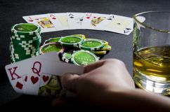 Person playing poker and looking at cards royalty free stock image