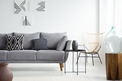 Black table next to grey couch with pillows in white flat interior with posters and chair. Real photo. Concept stock images