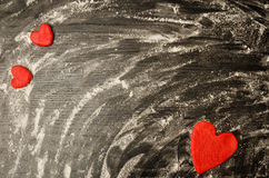 Black table of scattered flour. Red hearts of dough on the corners of the frame, place for text Stock Images