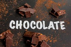 """Inscription """"chocolate"""" at dark table with chocolate powder stock images"""