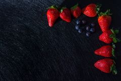 BLACK TABLE WITH TEXTURES WITH STRAWBERRY FRAMEWORK, BLUEBERRIES AND RED FRUITS royalty free stock photography