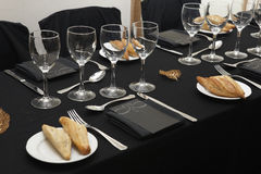 Black tablecloth with glasses and dishes. Stock Photo