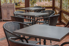 Black tables and chairs on street cafe on summer terrace.  Stock Photo