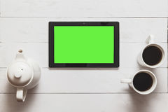 Black tablet with blank green screen and hot tea, teapot on loft wood table in cafe Royalty Free Stock Photo