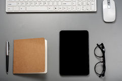 Black tablet computer with a keyboard, pen, glasses and notepad Stock Photography