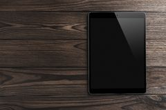 Black tablet computer on wooden dark background with space for text stock image