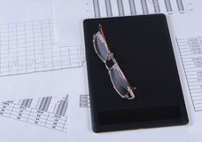 Black tablet with glasses lying on it in the financial tables and graphs Royalty Free Stock Image