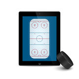 Black tablet with ice hockey puck and field on the screen. Royalty Free Stock Photos