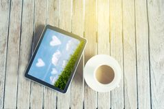 Black tablet ipad on table desk with coffee cup. Black smart tablet on table desk with coffee cup on wooden table stock images