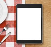 Black tablet pc on dinner table with blank screen Stock Image