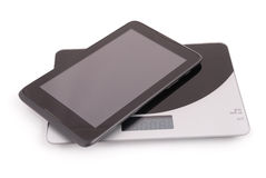 Black tablet pc isolated lies on the scales (Clipping path) Stock Images