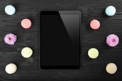 Black tablet pc looking similar to ipad and colorful macarons on old dark wood background. Top view, flat lay stock images