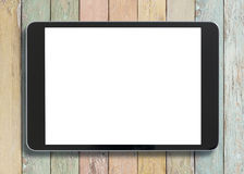 Black tablet pc looking similar to ipad on old colorful wood background. Black tablet pc looking similar to ipad on wood colorful background Stock Photo
