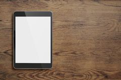 Black tablet pc on old wood table background Royalty Free Stock Photos