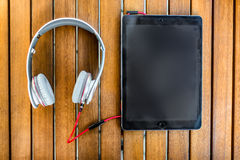 Black tablet PC and white headphones on the wooden background Royalty Free Stock Photos