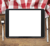 Black tablet pc on wooden table with fork and Stock Image