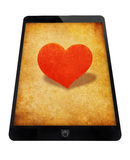Black tablet with red heart. Royalty Free Stock Images