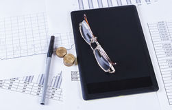 Black tablet ruchkaa and glasses lying on the financial tables and graphs stock photography