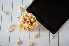 Black tablet touch computer gadget with popcorn on white wooden background. Stock Photos
