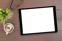 Black tablet white screen on table Royalty Free Stock Image